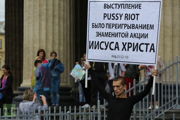 "Artist Pyotr Pavlensky holds a board in support of jailed members of female punk band ""Pussy Riot"" with his mouth sewn shut during a protest outside the Kazan Cathedral in St. Petersburg. (REUTERS / Trend Photo Agency / Handout)"