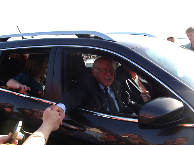 Bernie Sanders shakes the hands of supporters as he leaves the rally in his Jeep